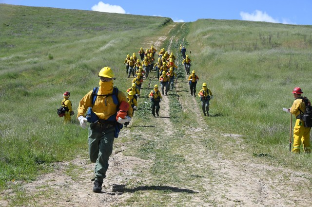 Cal Guard Soldiers from Task Force Rattlesnake run down a hill during wildland firefighting training March 28 at Camp Roberts. The run was part of fire shelter training.