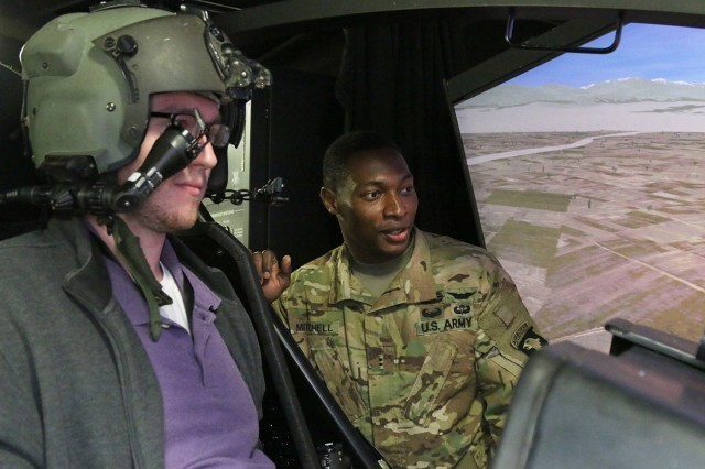 Chief Warrant Officer 2 Joseph Mitchell shows a participant of the Upward Leader Investment for Tomorrow (UpLIFT) class around the cockpit during the class' staff ride to Fort Campbell, Kentucky last year. (