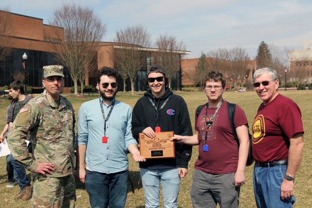 BLOOMSBURG, Pa. -- Staff Sgt. Gregory Guido (far left), an Army recruiter from the Hazleton Army Recruiting Station  for the Drone Wars presents a plaque to the overall winning team of this year's second annual Drone Wars competition in the open category consisted of (left to right) Dante Cicco, Dante Zitello, and Jacob McMahon of team ROCK from Slippery Rock University, Slippery Rock, Pa.