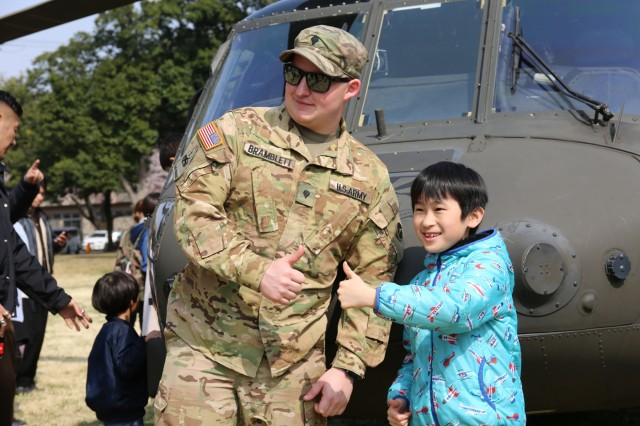 Spc. Matthew Bramblett, assigned to U.S. Army Aviation Battalion Japan, poses for a photo with a young visitor in front of a Black Hawk helicopter March 30 during Camp Zama's annual Cherry Blossom Festival. (U.S Army photo by Noriko Kudo)Maj. Brian Smith, assigned to U.S. Army Aviation Battalion Japan, poses for a photo opportunity with local children during the annual Cherry Blossom Festival, open post event, held on March 30, 2019 on Camp Zama. (U.S Army photo by Noriko Kudo)