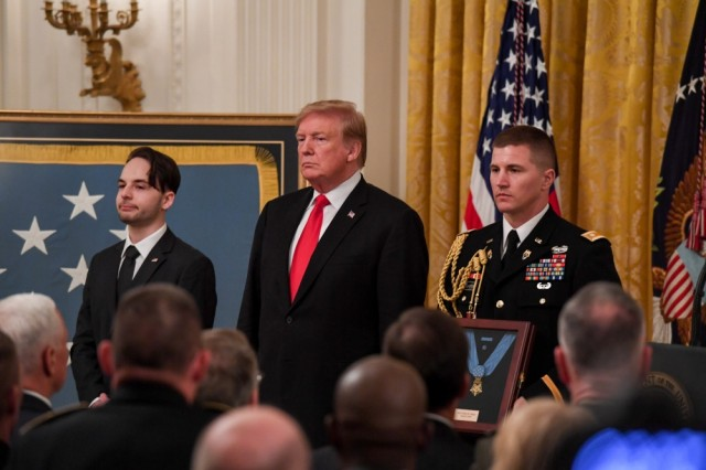 President Donald J. Trump, stands alongside Trevor Oliver, son of Staff Sgt. Travis Atkins, before awarding the Medal of Honor, at the White House in Washington D.C., March 27, 2019. Staff Sgt. Atkins was posthumously awarded the Medal of Honor for actions while serving with Delta Company, 2nd Battalion, 14th Infantry Regiment, 2nd Brigade Combat Team, 10th Mountain Division, in Abu Sarnak, Iraq, in support of Operation Iraqi Freedom, on June 1, 2007. His extraordinary heroism in attempting to subdue a suicide bomber and shielding three Soldiers from the imminent explosion resulted in him being mortally wounded and saving the Soldiers.