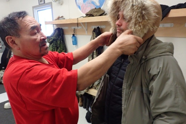 Roger Hitkolok, left, from the 1st Canadian Ranger Patrol Group, with Lt. Col. Michael Arnett, demonstrates how a fur ruff must encircle the face to properly protect cheeks and throat in the Arctic cold.