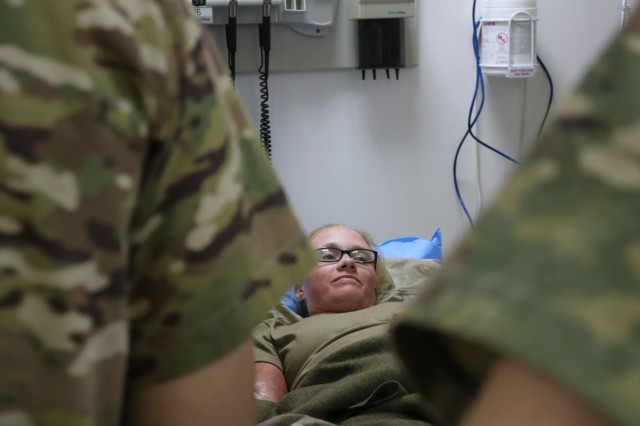 A mock casualty lies in a bed during the Golden Trident mass casualty training exercise at Camp Arifjan, Kuwait, March 21, 2019. (U.S. Army photo by Sgt. Nahjier Williams)