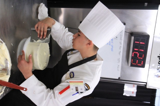 Spc. Raul Macuil, a culinary arts specialist, spreads a layer of cream cheese frosting during the Joint Culinary Training Exercise's Pastry Chef of the Year category at Maclaughlin Fitness Center on Fort Lee, Virginia March 12. The 44th annual JCTE, administered by the Joint Culinary Center of Excellence, started March 9, and ended March 14. The exercise is the largest American Culinary Federation-sanctioned competition in North America and showcases the talent of more than 200 military chefs from around the world. The Riverside, California native serves in 1st Battalion, 26th Infantry Regiment, 2nd Brigade Combat Team, 101st Airborne Division (Air Assault). (U.S. Army photo by Pfc. Lynnwood Thomas, 40th Public Affairs Detachment)