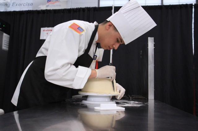 Spc. Raul Macuil, a culinary arts specialist, trims a layer of fondant during the Joint Culinary Training Exercise's Pastry Chef of the Year category at Maclaughlin Fitness Center on Fort Lee, Virginia March 12. The 44th annual JCTE, administered by the Joint Culinary Center of Excellence, started March 9, and ended March 14. The exercise is the largest American Culinary Federation-sanctioned competition in North America and showcases the talent of more than 200 military chefs from around the world. The Riverside, California native serves in 1st Battalion, 26th Infantry Regiment, 2nd Brigade Combat Team, 101st Airborne Division (Air Assault). (U.S. Army photo by Pfc. Lynnwood Thomas, 40th Public Affairs Detachment)