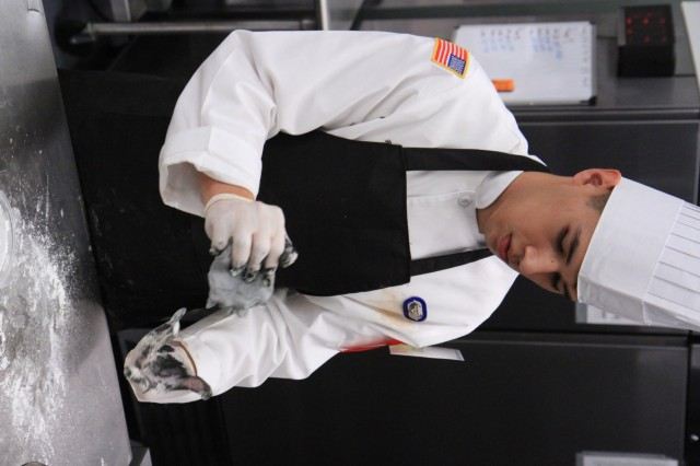 Spc. Raul Macuil, a culinary arts specialist, kneads fondant with food coloring during the Joint Culinary Training Exercise's Pastry Chef of the Year category at Maclaughlin Fitness Center on Fort Lee, Virginia March 12. The 44th annual JCTE, administered by the Joint Culinary Center of Excellence, started March 9, and ended March 14. The exercise is the largest American Culinary Federation-sanctioned competition in North America and showcases the talent of more than 200 military chefs from around the world. The Riverside, California native serves in 1st Battalion, 26th Infantry Regiment, 2nd Brigade Combat Team, 101st Airborne Division (Air Assault). (U.S. Army photo by Pfc. Lynnwood Thomas, 40th Public Affairs Detachment)
