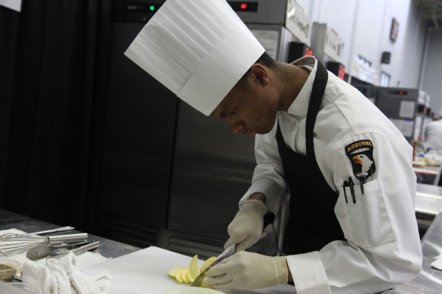 Pfc. Trevon Golden, a culinary arts specialist, seasons an arctic char and risotto during the Joint Culinary Training Exercise's Student Chef of the Year category at Maclaughlin Fitness Center on Fort Lee, Virginia March 14. The 44th annual JCTE, administered by the Joint Culinary Center of Excellence, started March 9, and ended March 14. The exercise is the largest American Culinary Federation-sanctioned competition in North America and showcases the talent of more than 200 military chefs from around the world. The St. Louis, Missouri native serves in 526 Brigade Support Battalion, 2nd Brigade Combat Team, 101st Airborne Division (Air Assault). (U.S. Army photo by Pfc. Lynnwood Thomas, 40th Public Affairs Detachment)