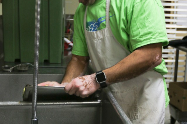 Spc. Moses Edwardo Morales, a Fort Campbell's BOSS volunteer from 2nd Battalion, 502 Infantry Regiment, 2nd Brigade Combat Team, 101st Airborne Division, washes pans that were used during the Manna Café' soup kitchen event Nov. 18.