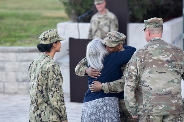 U.S. Army Reserve Maj. Gen. Jonathan Woodson, incoming commanding general of Army Reserve Medical Command, headquartered in Pinellas Park, Florida, hugs his wife, Sherril, following his promotion to major general in a ceremony, March 31. 2019. Maj. Gen. Scottie Carpenter, right, Deputy Commanding General, U.S. Army Reserve Command, presided over the promotion ceremony for Woodson, at a ceremony at the C. W. Bill Young Armed Forces Center in Pinellas Park, Florida. (U.S. Army Reserve photo by Anthony L. Taylor)