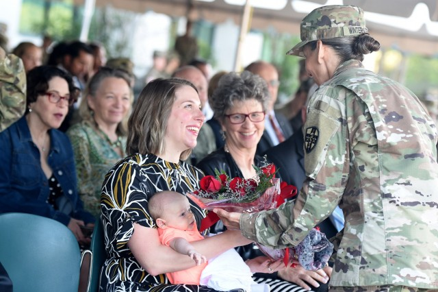 Sgt. First Class Theresa Winterhalter presents flowers to Kinsey Dona, Maj. Gen. Mary Link's daughter-in-law, who is holding grandson, Theodore, during Army Reserve Medical Command's change of command ceremony in Pinellas Park, Florida held on March 31, 2019. Link, outgoing commanding general for ARMEDCOM, relinquished command to Maj. Gen. Jonathan Woodson, incoming commanding general for ARMEDCOM, headquartered in Pinellas Park, Florida. The change of command ceremony symbolizes the continuation of leadership  and unit identity despite the change of individual authority. It also represents the transfer of power from one leader to another; passing the ceremonial flag from outgoing to incoming commander is a physical representation of that transfer. (U.S. Army Reserve photo by Anthony L. Taylor)