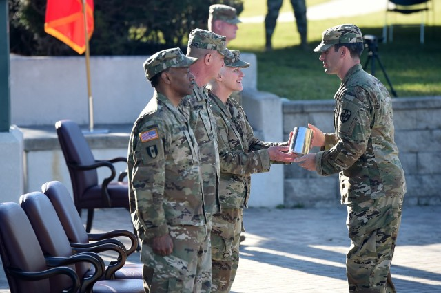 Capt. William Bishop, right, presents a ceremonial artillery round casing to Maj. Gen. Mary E. Link, outgoing commanding general of Army Reserve Medical Command, during a change of command ceremony held in Pinellas Park, Florida on March 31, 2019. Link relinquished command to Maj. Gen. Jonathan Woodson, incoming commanding general for ARMEDCOM.  The change of command ceremony symbolizes the continuation of leadership and unit identity despite the change of individual authority. It also represents the transfer of power from one leader to another; passing the ceremonial flag from outgoing to incoming commander is a physical representation of that transfer. (U.S. Army Reserve photo by Anthony L. Taylor)