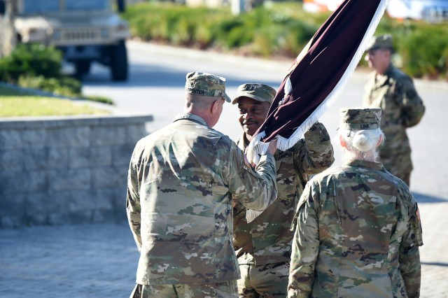 U.S. Army Reserve Maj. Gen. Jonathan Woodson, incoming commanding general of Army Reserve Medical Command, receives the command's colors from Maj. Gen. Scottie Carpenter, deputy commanding general for U.S. Army Reserve Command, during a Change of Command ceremony held on Sunday, March 31, 2019 in Pinellas Park, Florida.  The change of command ceremony symbolizes the continuation of leadership  and unit identity despite the change of individual authority. It also represents the transfer of power from one leader to another; passing the ceremonial flag from outgoing to incoming commander is a physical representation of that transfer. (U.S. Army Reserve photo by Anthony L. Taylor)