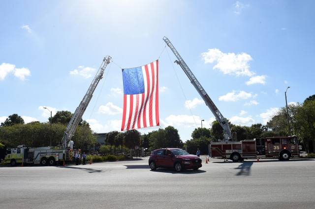 U.S. Army Reserve Maj. Gen. Mary E. Link, outgoing commanding general of Army Reserve Medical Command, departs the C. W. Bill Young Armed Forces Center, under a large American flag, hoisted by Pinellas Park Fire Station 35, following her Change of Command ceremony on March 31, 2019. Link relinquished command to Maj. Gen. Jonathan Woodson, the incoming commanding general for ARMEDCOM, during the ceremony.  The change of command ceremony symbolizes the continuation of leadership  and unit identity despite the change of individual authority. It also represents the transfer of power from one leader to another; passing the ceremonial flag from outgoing to incoming commander is a physical representation of that transfer. (U.S. Army Reserve photo by Anthony L. Taylor)