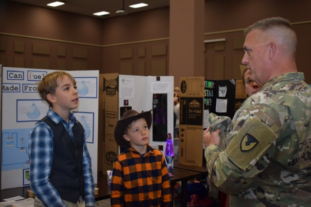 Crane Army Ammunition Activity Commander Col. Michael Garlington asks a student about his award-winning project at the 35th Annual Team Crane Science Fair April 4, 2019.