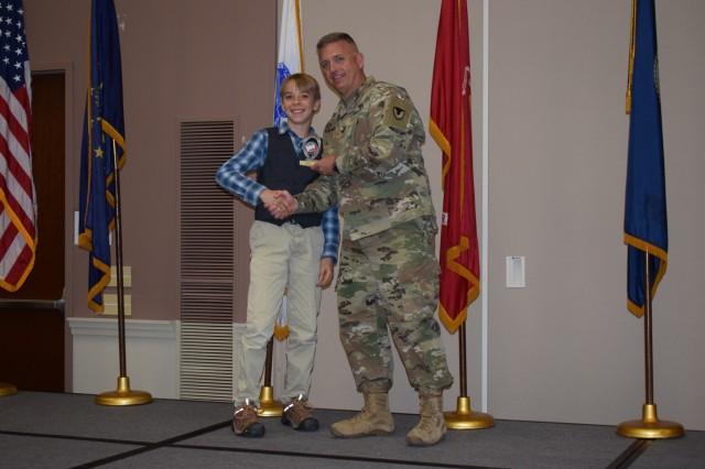 Crane Army Ammunition Activity Commander Col. Michael Garlington presents a trophy to a student at the 35th Annual Team Crane Science Fair April 4, 2019.