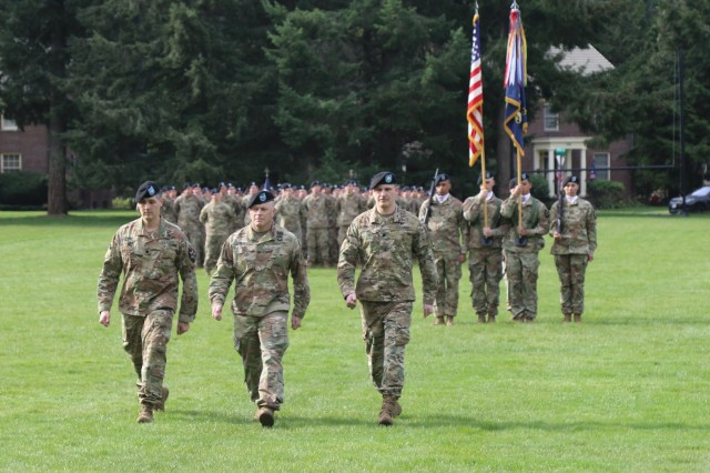 Col. Jay Miseli, 2nd Stryker Brigade Combat Team, 2nd Infantry Division commander, leaves the field with incoming commander of 2nd Battalion, 1st Infantry Regiment, Lt. Col. Blake Wetherell (right) and outgoing commander, Lt. Col. Charles Ford (left) after completing the passing of colors signifying the transfer of authority and command at Joint Base Lewis-McChord, WA, April 2, 2019.