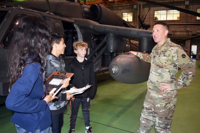 Sgt. Maj. Kyle Clutter, right, assigned to the U.S. Army Aviation Battalion Japan, speaks to students from John O. Arnn Elementary School during a job shadowing event at Camp Zama April 4.