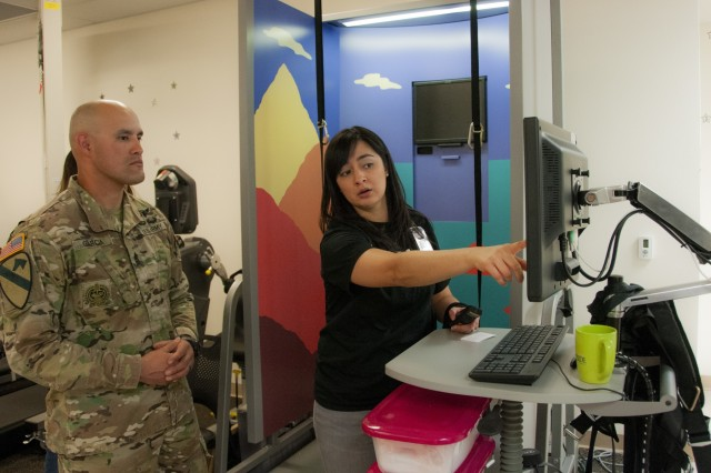 Nancy Silva, physical therapist, Fort Bliss Traumatic Brain Injury (TBI) Clinic, William Beaumont Army Medical Center, explains results of a neuro-sensory exam evaluating center of balance to 1st Sgt. Nicolas Garcia, first sergeant, Headquarters and Headquarters Troop, 1st Squadron, 1st Cavalry Regiment, 2nd Brigade Combat Team, 1st Armored Division, during the TBI Clinic's open house event, March 29, in observance of Brain Injury Awareness Month.