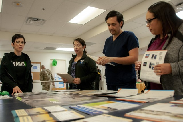 Elizabeth Fuentes (left), physical therapist assistant, Fort Bliss Traumatic Brain Injury (TBI) Clinic, William Beaumont Army Medical Center, provides information and educates medical professionals about TBI symptoms, treatments and assessments, during the TBI Clinic's open house event, March 29, in observance of Brain Injury Awareness Month.