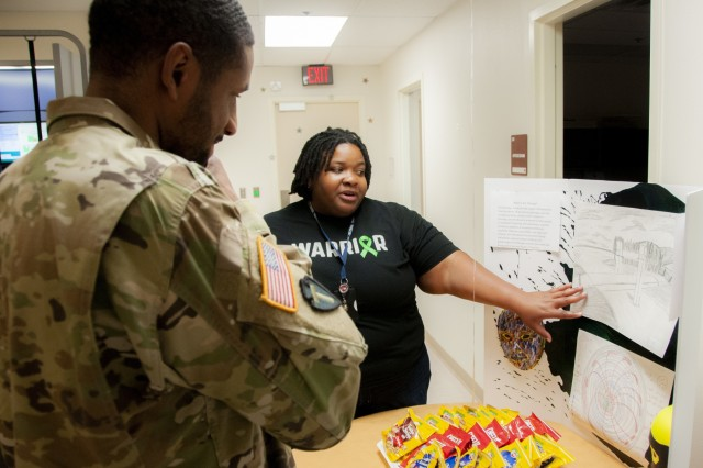 Nedra Warren, art therapist, Fort Bliss Traumatic Brain Injury (TBI) Clinic, William Beaumont Army Medical Center, discusses art therapy as a stress management tool to Spc. Jeremy Jefferson, signal support system specialist, Training Support Battalion, during the TBI Clinic's open house event, March 29, in observance of Brain Injury Awareness Month.