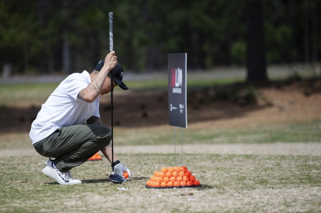 Sgt. Emmanuel Quaimbao, 1st Armored Division, tees up his golf ball during the qualifier.
