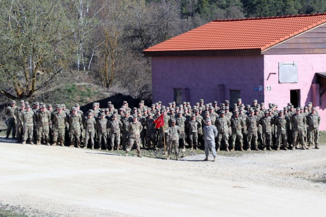 Soldiers assigned to the 372nd Engineer Company, U.S. Army Reserves, out of Pewaukee, Wisconsin, pose for a unit photo in front of a gable roof their build on an existing flat roof during their annual training at Joint Multinational Readiness Center in Hohenfels, Germany, April 4, 2019. The 372nd spent their annual training improving multiple sites in the training  area on JMRC.