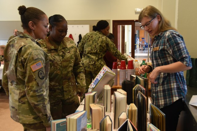 """Sophie Dorn (right), library technician at the SHAPE International Library, shows Army Col. Yolonda """"YR"""" Summons, SHAPE Healthcare Facility commander, and Army Sgt. Maj. Delonica Boyce, operations sergeant major for Headquarters, U.S. NATO SHAPE, library books featuring women leaders during the Women's History Month observance, March 27, 2019, at SHAPE, Belgium. During the event, female leaders spoke about how they overcame adversity in the military and the importance of fostering diversity."""