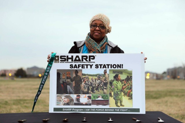 Monica Carr, Sexual Assault Response Coordinator (SARC), assigned to the 704th Military Intelligence Brigade behind the Safety Station holding a guidon streamer, during the Sexual Harassment and Assault Response and Prevention (SHARP) Challenge, April 5 at Fort Meade's McGlachlin parade field, Maryland.