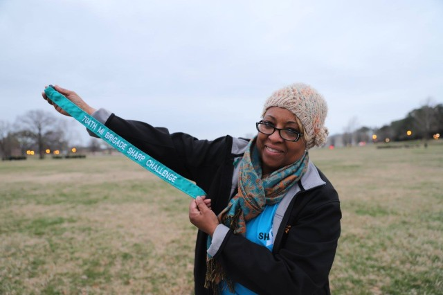 Monica Carr, Sexual Assault Response Coordinator (SARC), assigned to the 704th Military Intelligence Brigade holds a guidon streamer, during the Sexual Harassment and Assault Response and Prevention (SHARP) Challenge, April 5 at Fort Meade's McGlachlin parade field, Maryland.