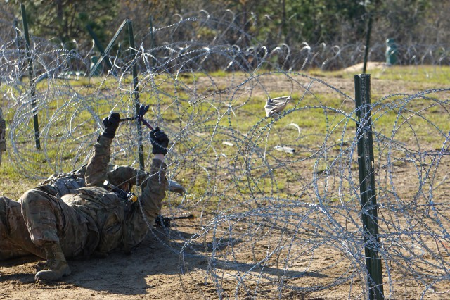 A Sapper cuts through a concertina wire obstacle before emplacing an explosive charge to breach a barrier for the advancing infantry company during the 1BCT CALFEX on OP13 at Fort Bragg, March 25 through April 6, 2019.