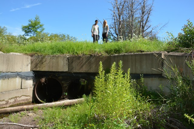 2016 photo of the old culvert that had two circular pipes with a total diameter of 36 inches. Pictured are Rifat Salim (left) and JoAnne Castagna, Public Affairs.