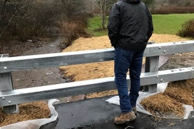 Graydon Dutcher looking over the new culvert that is successfully working in torrential rain conditions.