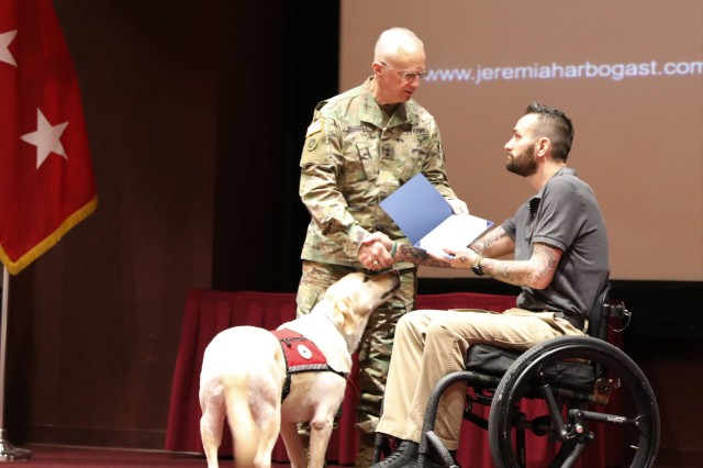 Maj. Gen. Allen Harrell of the Army Materiel Command commends Jeremiah Arbogast for sharing his story of sexual assault during the April 2, 2019, Team Redstone kickoff for Sexual Assault Awareness and Prevention Month at Redstone Arsenal, Ala. With them is Arbogast's medical working dog.
