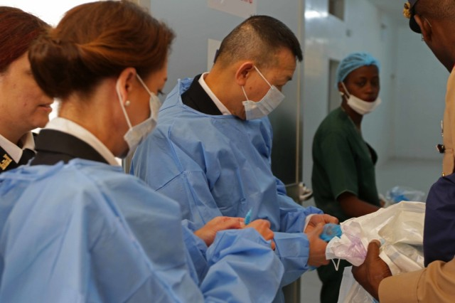 U.S. Army Africa Deputy Commanding General Brig. Gen. Lapthe Flora and U.S. Embassy of Senegal Defense Attache' Col. Gwyn Carver prepare to observe surgery at the Hospital Military De Ouakam, Senegal, during Medical Readiness Exercise 19-2, 8 April 2019. Medical Readiness Exercises provide a real-world environment where medical professionals from both militaries can build and strengthen medical treatment capability and capacity by honing their medical skills in alternative conditions while also learning different protocols from their counterparts.