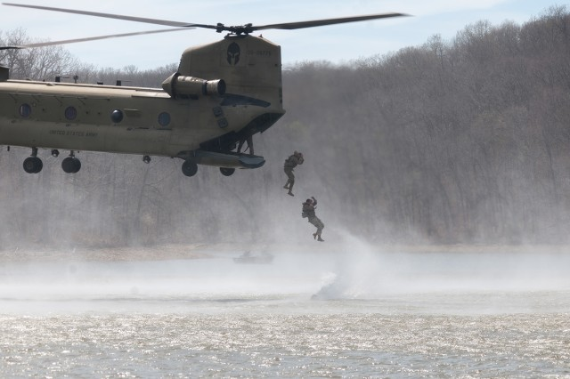 A team of Best Sapper competitors plunges into the Lake of the Ozarks from the back of a Boeing CH-47 Chinook.