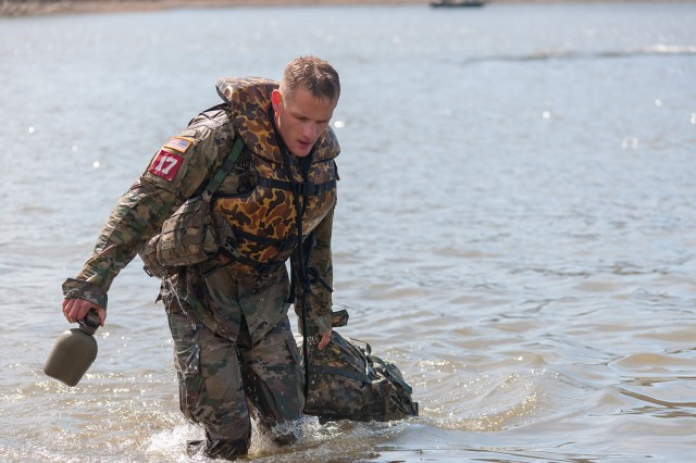 Capt. John Baer, 39th Brigade Engineer Battalion, of Fort Campbell, Kentucky, pulls himself and his ruck sack ashore following the drop by helicopter at the Lake of the Ozarks.