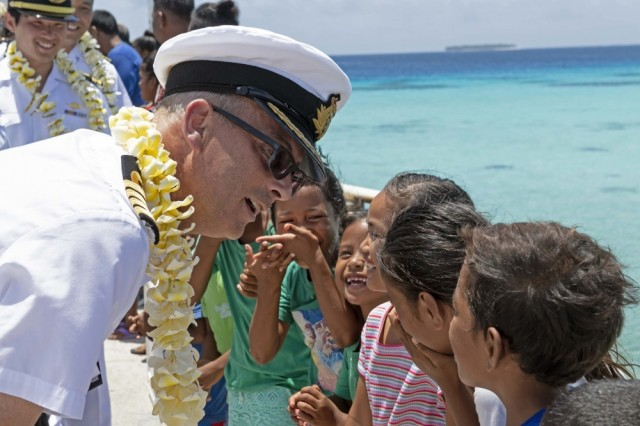 ENNIBURR, Republic of the Marshall Islands (March 26, 2019) Royal Navy Capt. Paddy Allen, director of mission, talks with Marshallese children on the Enniburr pier after arriving for a ground-breaking ceremony during Pacific Partnership 2019. Pacific Partnership, now in its 14th iteration, is the largest annual multinational humanitarian assistance and disaster relief preparedness mission conducted in the Indo-Pacific. Each year, the mission team works collectively with host and partner nations to enhance regional interoperability and disaster response capabilities, increase stability and security in the region, and foster new and enduring friendships in the Indo-Pacific.