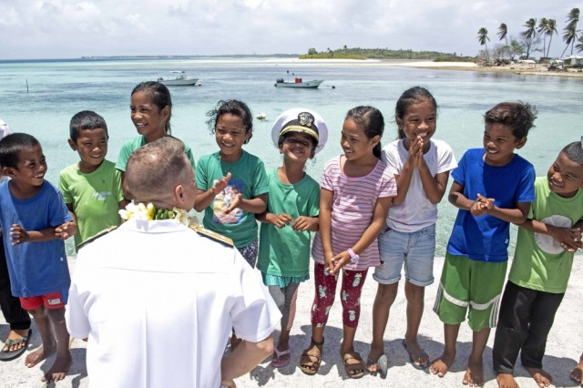 ENNIBURR, Republic of the Marshall Islands (March 26, 2019) Rear Adm. Joey Tynch, Commander, Task Force 73, talks with Marshallese children on the Enniburr pier after arriving for a ground-breaking ceremony during Pacific Partnership 2019. Pacific Partnership, now in its 14th iteration, is the largest annual multinational humanitarian assistance and disaster relief preparedness mission conducted in the Indo-Pacific. Each year, the mission team works collectively with host and partner nations to enhance regional interoperability and disaster response capabilities, increase stability and security in the region, and foster new and enduring friendships in the Indo-Pacific.