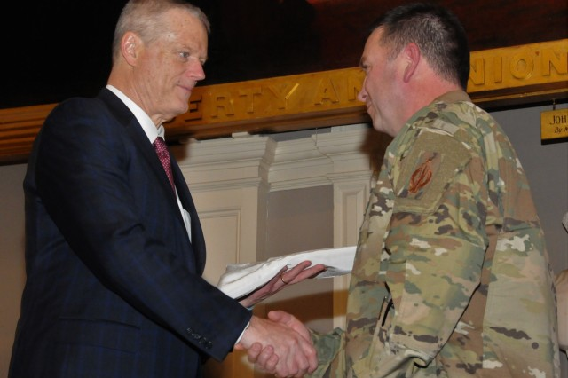 Massachusetts Governor Charlie Baker, left, receives a flag from Maj. Gen. Gary Keefe, adjutant general of the Massachusetts National Guard, during the April 8 kickoff event for the U.S. Army's first-ever Army Week in Boston. Army Week - Boston is a Total Army community outreach effort to connect the Boston community and its citizens with the Army they haven't met yet.