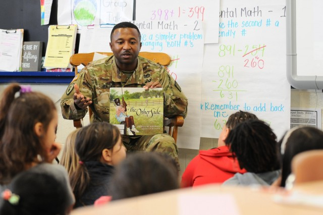 "Staff Sgt. Robert Palmer, operations sergeant for 20th Chemical, Biological, Radiological, Nuclear, Explosives (CBRNE) Command reads 'The Other Side' to a class of students at Roye-Williams Elementary School. Elementary schools across the nation celebrated 'Read Across America' during the month of March which ""calls for every child in every community to celebrate reading"" and recognizes children's author, Dr. Seuss, whose birthday is March 2."