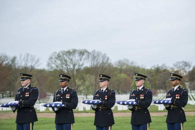 Soldiers from the 3d U.S. Infantry Regiment (The Old Guard) hold folded U.S. flags as part of military funeral honors with funeral escort for U.S. Army Chief Warrant Officer 2 Jonathan Farmer in Section 60 of Arlington National Cemetery, Arlington, Virginia, April 9, 2019.Farmer joined the Army on March 30, 2005 and graduated in 2007 from One Station Unit Training at Fort Benning, Georgia to become a Special Forces engineer sergeant. He earned his commission as a Special Forces warrant officer in 2016 and after graduation for the basic Special Forces Warrant Officer Course, was then selected to serve as an assistant detachment commander.Farmer had previously served five combat tours in Iraq and Afghanistan, before deploying to Syria in early January 2019. Farmer died of wounds sustained during an attack while conducting a local engagement in Manbij, Syria, January 16, 2019. Also killed in the attack were U.S. Navy Chief Petty Officer Shannon Kent, and Defense Intelligence Agency civilian Scott Wirtz.His spouse, Tabitha Farmer, received the U.S. flag from his casket, and folded U.S. flags were presented to his four children and parents.(U.S. Army photo by Elizabeth Fraser / Arlington National Cemetery / released)