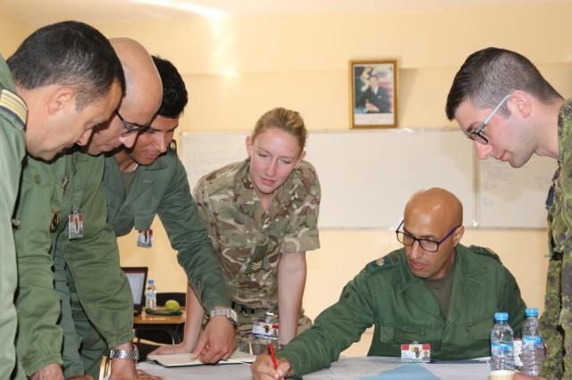 Royal Moroccan Armed Forces soldiers, along with a U.K. and a Canadian soldier, gather around a map to make a plan March 27, 2019, during the command post exercise portion of exercise African Lion 2019 at the Southern Headquarters Zone in Agadir, Morocco. African Lion 2019 is a Chairman of the Joint Chiefs of Staff-sponsored, U.S. Africa Command-scheduled and U.S. Marine Corps Forces Europe and Africa-led exercise concentrated in Morocco with an element in Tunisia.