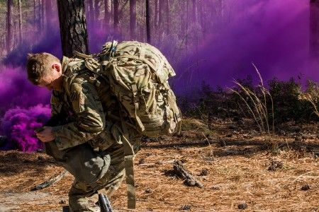 An Expert Field Medical Badge candidate reaches for his mask after a simulated chemical attack during lane testing at Fort Bragg, N.C., March 14, 2019. Soldiers participating in the competition must don gas masks within nine seconds to proceed in the qualification for the Army special skills badge.