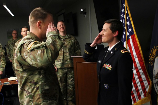 Newly appointed Warrant Officer Natalie Wamsley salutes her husband, Chief Warrant Officer Ronald Wamsley, during a commissioning ceremony in Frankfort, Ky., March 19, 2019. Wamsley completed warrant officer candidate school March 1 while battling cancer.