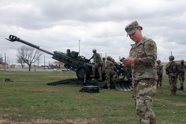 On a mission to find ambient sounds for her new overture celebrating 150 years of Fort Sill history, Chief Warrant Officer 2 Bridgette Brenmark, commander of the 77th Army Band at Fort Sill, Okla., attempts to record the chatter of Soldiers of C Battery, 1st Battalion, 78th Field Artillery on the windy afternoon of April 3, 2019, as they practice loading a Triple 7 howitzer.