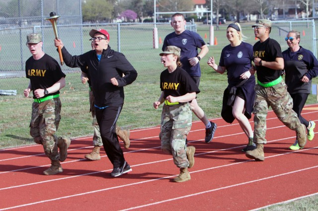 "Soldiers cheer on Austin Crawford, 17, of Cache, Okla., torchbearer for the ""Parade of Stars"" that kicked off the 10th annual Great Plains Region Special Olympics hosted by 30th Air Defense Artillery Brigade at Fort Sill, Okla."