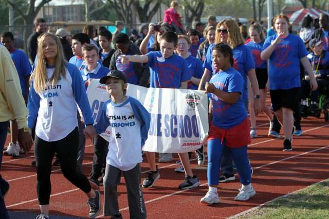 """Proud Autism Mom"" Sandra Summerfield joins hands with her 7-year-old son, Peyton, a second grader at Freedom Elementary School, to march in the Great Plains Region Special Olympics parade April 5, 2019, on the Prichard Field running track at Fort Sill, Okla."