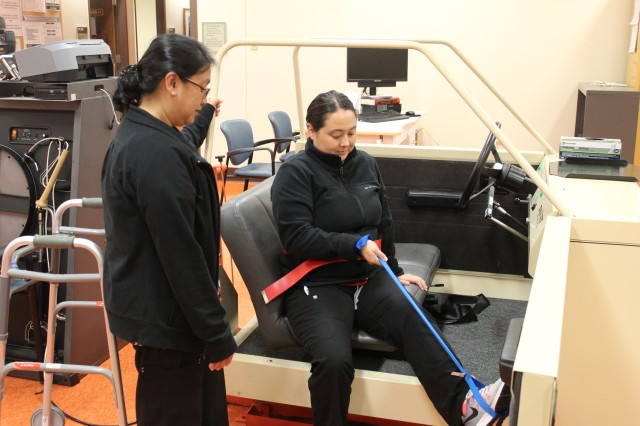 Julie Gurtiza, left, certified occupational therapy assistant, Tripler Army Medical Center, oversees Nicola Morimoto with proper car transfer training at the TAMC OT Clinic on Feb. 23.