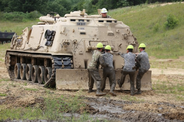 Students in the Regional Training Site-Maintenance Tracked Vehicle Recovery Course pull out a two cable during course training July 19, 2018, at Fort McCoy, Wis. Training like this was a factor in Fort McCoy's estimated $1.135 billion economic impact to the local economy for fiscal year 2018. (U.S. Army Photo by Scott T. Sturkol)