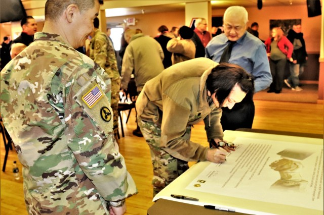 Garrison Commander Col. Hui Chae Kim, and Deputy to the Garrison Commander James A. Chen watch Garrison Deputy Commander Lt. Col. Sheila L. Coker sign the Installation Management Command (IMCOM) Leadership Pledge on Jan. 23, 2019, in building 905 at Fort McCoy, Wis. The pledge is part of IMCOM's Service Culture Initiative. IMCOM also breaks done the initiative into an acronym called SERVICE that acknowledges the command's principles - service, excellence, respect, vision, integrity, communication, and empowerment. It's also commitments like this that helped Fort McCoy earn a Bronze Award for the 2019 Army Communities of Excellence competition. (U.S. Army Photo by Scott T. Sturkol, Public Affairs Office, Fort McCoy, Wis.)